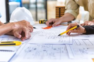 a team of contractors looking over blueprints on a desk